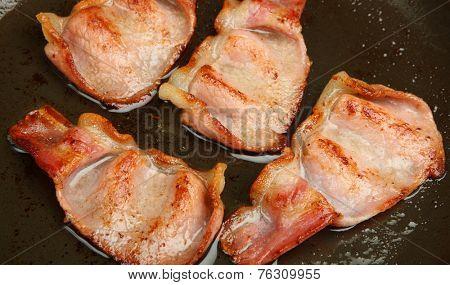 Bacon rashers frying in a non-stick pan.