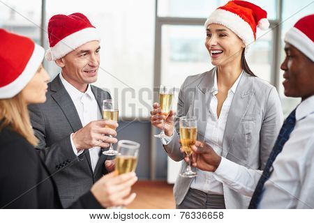 Happy business partners in Santa caps holding flutes with champagne at corporate party