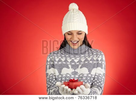 Astonished girl in winterwear looking at small giftbox on her gloved palms