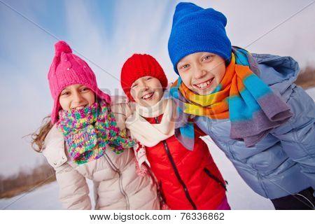 Happy little friends in winterwear looking at camera outside