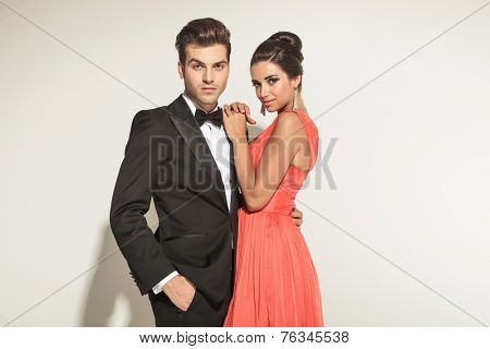 Elegant business man holding one hand in pocket while his girfriend is leaning on him.