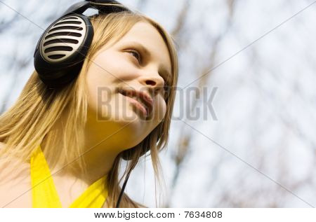 Blond woman listening music in headphones