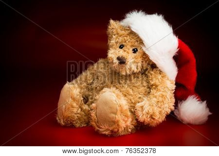 A Brown Teddy Bear Wearing A Christmas Hat