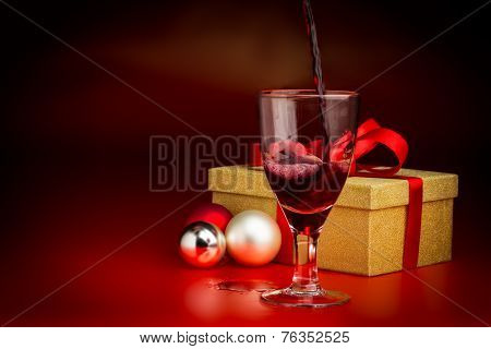Red Wine Poured Into Glass In Front Of Golden Present