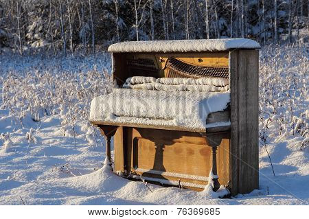 Upright piano that has been abandoned in a snowy winter field / meadow. poster
