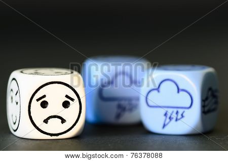 Concept Of Sad Storm Weather - Emoticon And Weather Dice On Black Background