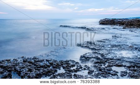 Rocky seashore and calm blue ocean under a cloudy sky with a shelf of rock jutting out into the sea. poster