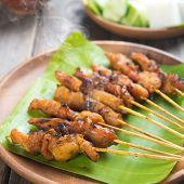 Yummy chicken sate or satay, skewered and grilled meat, served with peanut sauce. Fresh cooked with steamed and smoke. Hot and spicy Asian dish.  poster