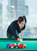 Young man playing billiards in billiard club poster