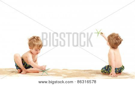Two toddler boys playing in beach sand with starfish, isolated on white