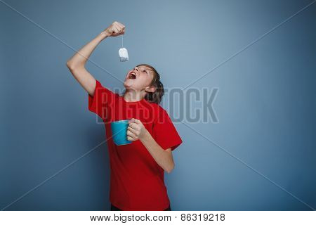 boy teenager European appearance in a red shirt holding a cup of