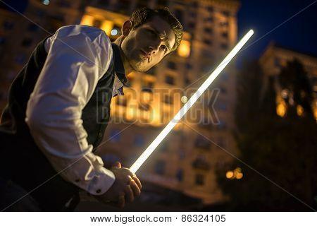Handsome guy holding a lightsaber Jedi