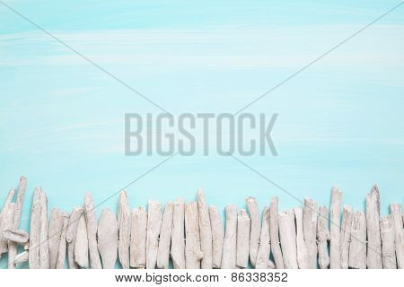Blue or turquoise oceanic background with a fence of driftwood for maritime decorations.