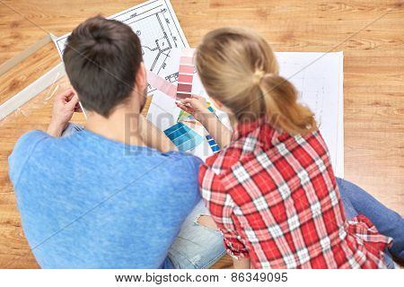 design, repair, decoration and people concept - close up of couple with blueprint and color samples sitting on floor at home