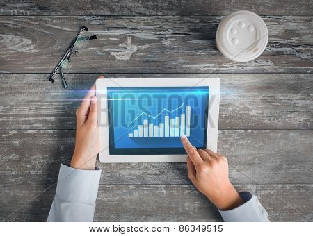 business, people, statistics and technology concept - close up of hands pointing finger to tablet pc computer screen with virtual graph, coffee cup and eyeglasses on table