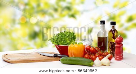 cooking, still life, food and healthy eating concept - fresh ripe vegetables, spices and kitchenware on table over green background
