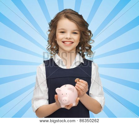 people, money, finances and savings concept - happy girl holding piggy bank and coin over blue burst rays background