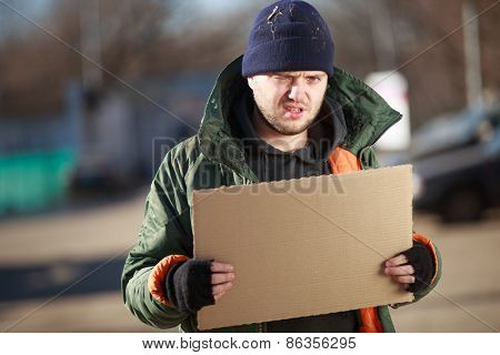 Homeless man holds blank cardboard for your own text