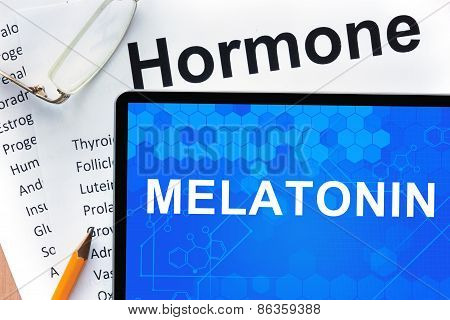 Papers with hormones list and tablet  with words melatonin.