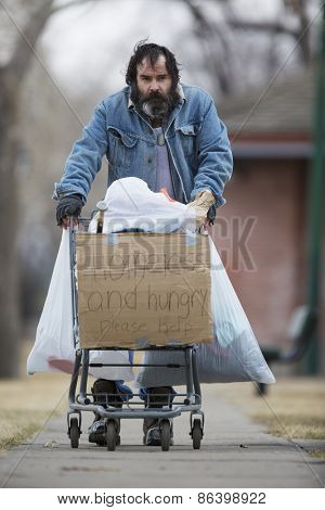 Homeless man with beard pushing a shopping cart with all his possessions.