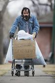 Homeless man with beard pushing a shopping cart with all his possessions. poster