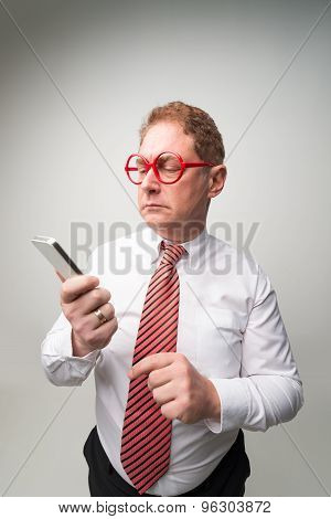Confused middle-aged businessman looking at the smartphone poster