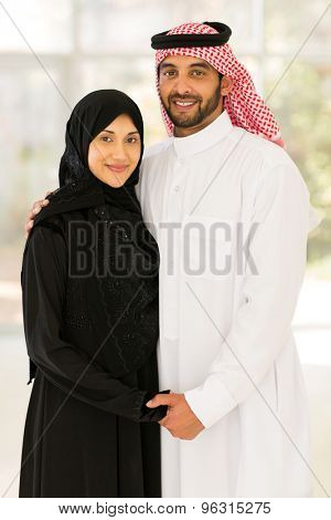beautiful young muslim couple holding hands at home
