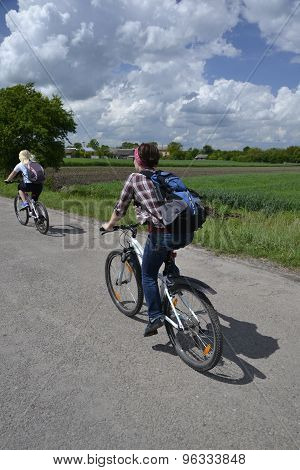 Two Girls On A Bicycles Ride Across A Coutryside