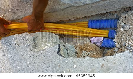 fiber optic cables buried in a micro trench by a worker