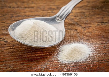 collagen protein powder on a tablespoon against rustic wood