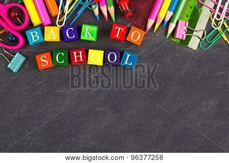 Back to School wooden blocks with school supplies border on blackboard