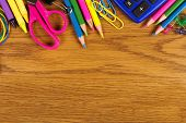 School supplies top border on a wood desk background poster