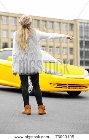 Woman catching yellow taxi cab on the street