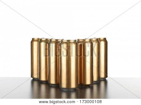 Cans of beer on table against white background
