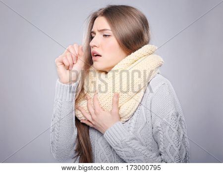 Young ill woman on color background