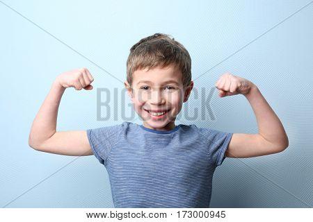 Portrait of little boy on light blue background