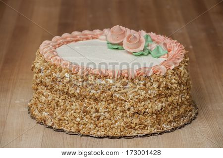 A decorated Italian cream cake with nuts on the side