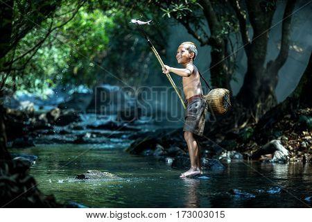 Asian Boy fishing in a creek in thailand
