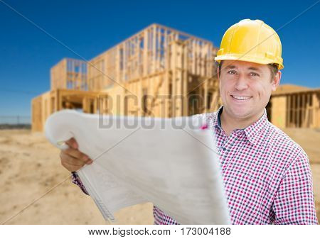 Smiling Contractor Wearing Hardhat Holding Blueprints at Home Construction Site.