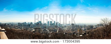 Montreal, Canada - April 17, 2016: Montreal city daytime skyline panorama over river with urban buildings. Image is taken from Mount Royal.