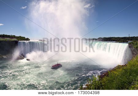 NIAGARA FALLS, CANADA - JUNE 12, 2016: The famous Horseshoe Falls with boat tour. This is North America's oldest attraction, since 1846. Niagara Falls, Canada.