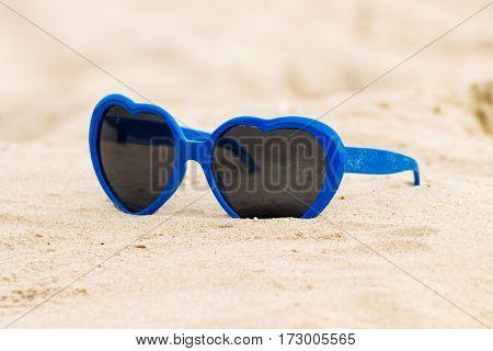 Blue Sunglasses Shaped Heart On The Sand