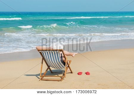 Happy woman in white sunhat on the beach sitting on deckchair .Vacation and travel concept.