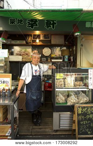 TOKYO-JAPAN, 27 June 2016: Smiling and proud japanese man standing in his restaurant at tsukiji fish market in Tokyo, japan. The biggest wholesale fish and seafood market in the world.