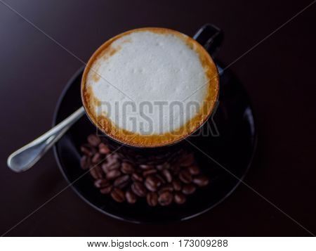 closeup cappuccino coffee on black cup with coffee bean on dark background