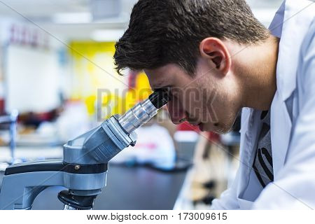 a young medical or scientific researcher or doctor looking through a microscope, a male researcher working in a lab, side view of male medical worker in research laboratory