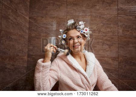 Young attractive housewife in the bathroom. A girl in a bathrobe and curlers doing morning makeup