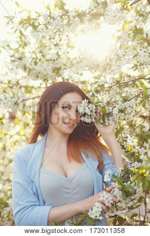 Pretty attractive girl in blossoming apple trees. Spring mood.