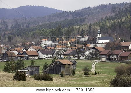 Picturesque village in the Slovenian mountains. Old style buildings and a beautiful barn and church.