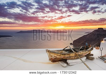 Old wooden fishermans''s boat on roofof house in Firostefani village with typical white architecture, Santorini island, Greece, during sunset over sea.